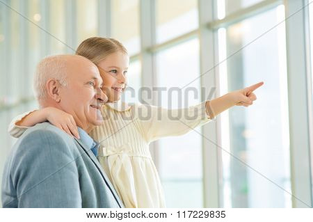 Grandfather holding his granddaughter and communicating.