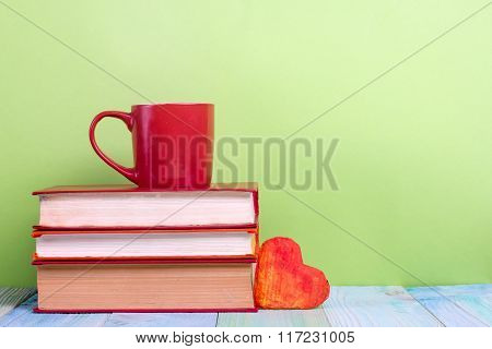 Stack of hardback books, diary on wooden deck table and green background. Back to school. Copy Space
