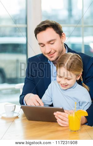Shot of nice father and cute daughter using tablet