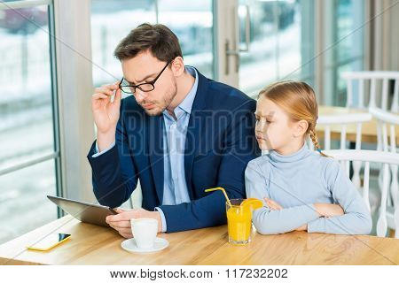 Young father and nice daughter working on the tablet.
