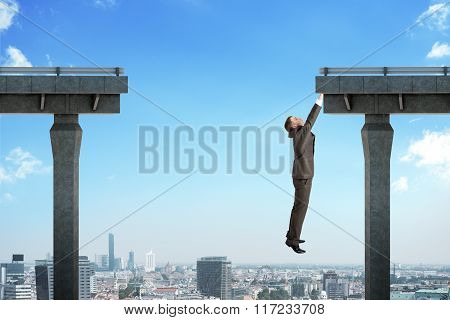 Businessman hanging out of bridge