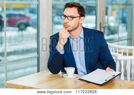 Young man sitting at the table with documents and coffee.