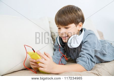 Nice boy relaxing on the sofa with phone and headset.