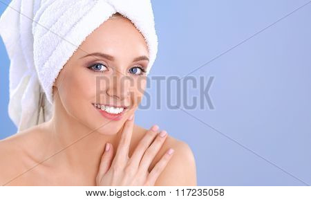 Beautiful woman with a towel on her head on a gray background