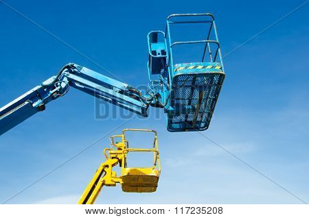 Two crane's baskets against clear sky. Lifters in blue and yellow