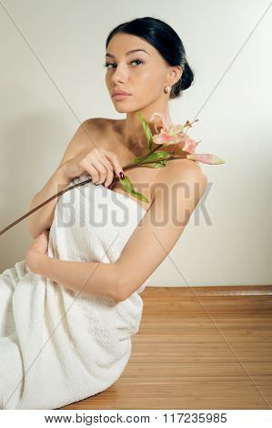 Beautiful lady with lilly flower. Perfect skin.