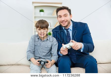 Handsome father enjoys playing video games with adorable son