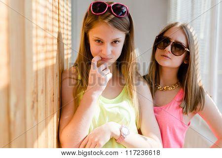 Two beautiful blond teenage girls having fun happy smiling