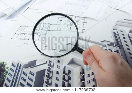 Architectural blueprints, blueprint rolls and magnifying glass on white background.