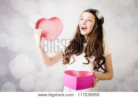 Beautiful young lady looking at heart box on bokeh background