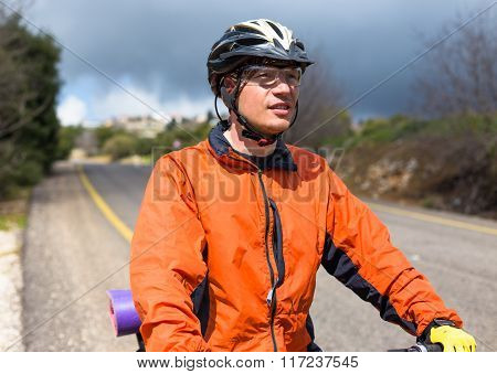 Male cyclist riding bike along road. Sunny day