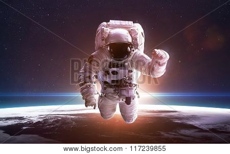 Astronaut in space over the planet Earth. Elements of this image furnished by NASA