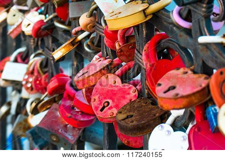 Love locks in the shape of heart painted red color on bridge