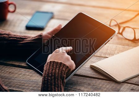 Opening the world with single touch. Close-up image of young woman holding digital tablet with copy space while sitting at the rough wooden table ** Note: Shallow depth of field