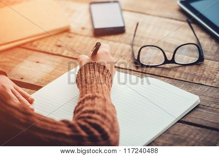 Planning new day. Close-up image of woman writing in notebook with copy space while sitting at the rough wooden table