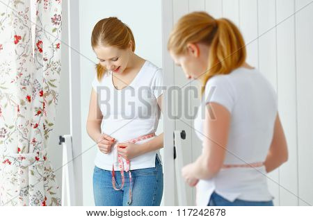 Woman Measuring Waist  In Front Of Mirror