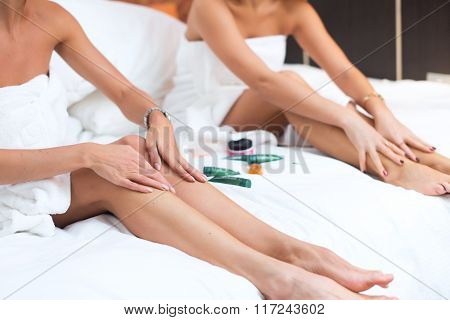 Women sitting on a bed applying moisturizer cream legs.