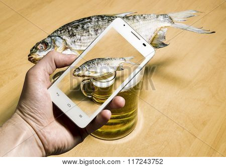 View Of The Mug With Beer And Dried Fish Through The Camera Of A Smartphone