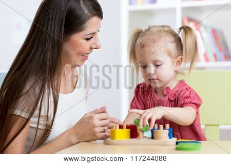 mother and kid playing logical toys at home