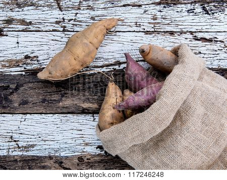 Harvested Organic Sweet Potatoes In A Hemp Sack Bag On Rustic Wood Table.