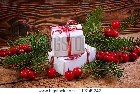 Christmas Presents Decorated With Pine Brushes And Red Berries