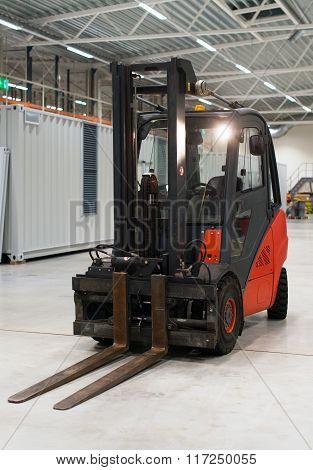 Orange forklift loader in the modern warehouse.