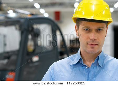 Warehouseman in yellow hard hat at warehouse.