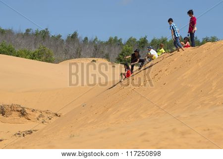 Children ride on the Red dunes. The Surroundings of Mui Ne, Vietnam