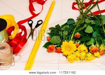 Workplace Of Florist, Making Bouquet. Yellow And Orange Roses On A Light Wooden Background.