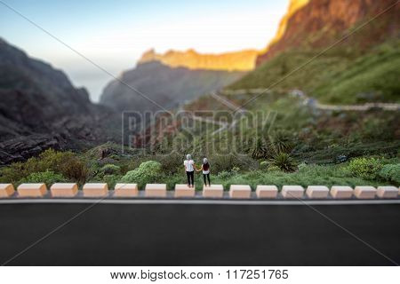 Carefree couple standing on the mountain roadside