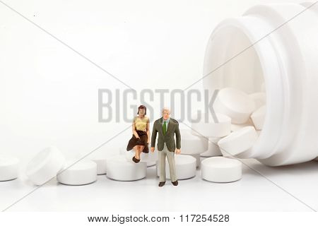 miniature people  - Elderly people posing in front of pills