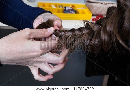 weaving braids girl in a hairdressing salon