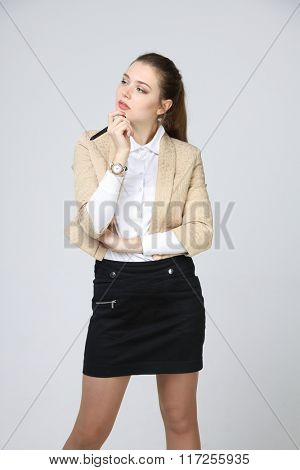 Young business woman thinking, holding pen in hand