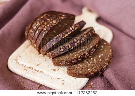 Sliced Dark Bread With Crumbs On Wood Board