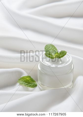 The moisturizing cream with green young leaves on the white silk