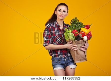 Young woman with a grocery shopping bag. Isolated on yellow background.