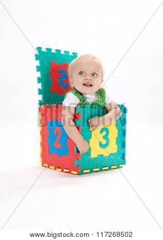 little child baby smiling sitting in the box playing with numbers isolated on white studio shot