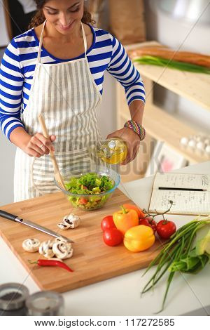 Young woman mixing fresh salad standing near desk