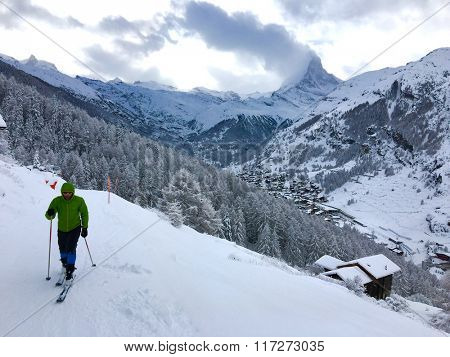 Man asceding on touring skis at beautiful winter landscape with fresh snow. Switzerland Alps, Zermatt, Materhorn mountain in background
