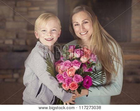 Smiling Boy giving his mom a bouquet of beautiful pink roses
