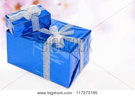 Celebration Concepts. Two Blue Wrapped Up Gift Boxes Standing Together. Against Flowery  Background.