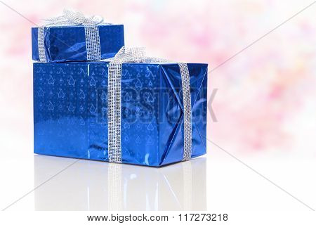 Celebration Concepts. Two Blue Wrapped Up Gift Boxes Standing Together. Against Flowery  Background