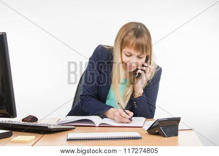 Business Woman Talking On The Phone In The Office Writes Book
