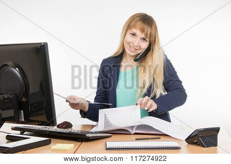 Business Woman Talking On The Phone And Looking For The Desired Paper Documents