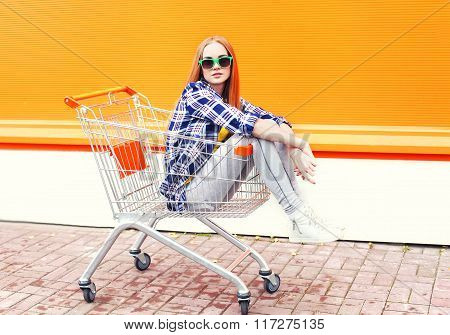 Fashion Cool Girl Sitting In Shopping Trolley Cart Over Colorful Background