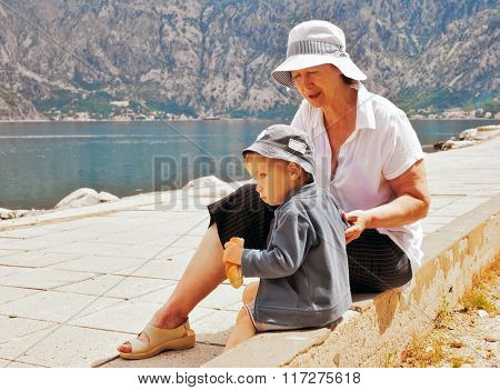 Sitting boy eats bread next to his grandmother