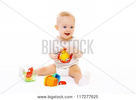 Happy Smiling Baby Playing With Toys On White Background