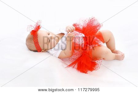 Beautiful Little Girl Baby In Red Skirt Lying On Bed