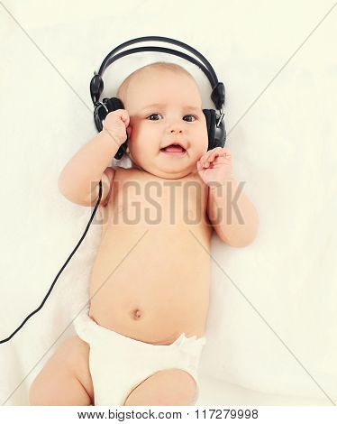 Cute Baby Listens To Music In Headphones Lying On Bed, Top View