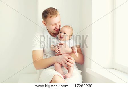 Happy Smiling Young Father And Baby At Home In White Room Near Window